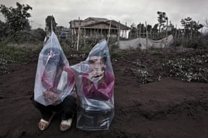 Mount Sinabung: Two boys wear plastic bags to protect themselves from ash