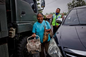 Mount Sinabung: A woman carries provisions as residents are evacuated from their village to