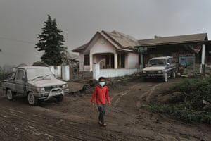 Mount Sinabung: A child stands outside an ash-covered house