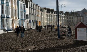 Aberystwyth promenade seen littered with debris following days of high tides and storms.  Much of the seafront has been severely damaged by the pounding of the waves, with the likely cost of repairs running into the millions of pounds.