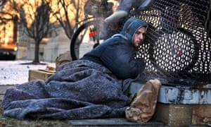 Nicholas Simmons, 20, of Greece, NY,  warms himself on a steam grate with three homeless men by the Federal Trade Commission, just blocks from the Capitol, during frigid temperatures in Washington on 4 January .