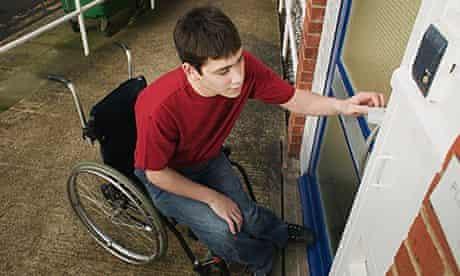 Man in wheelchair opening door