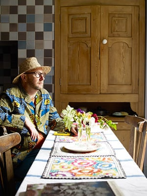 Homes - Hollicks house: Man dressed in blue and yellow jacket and straw hat sitting in kitchen