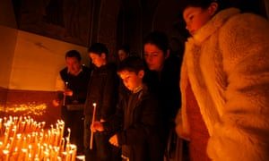 Children lighting prayer candles as they arrive at Serbian Orthodox Christians celebrating the Nativity of Christ liturgy at the Lazarica Church in Bournville, Birmingham.