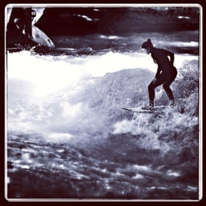 Young woman surfs on a permanent wave on the famous Eisbach river in Munich