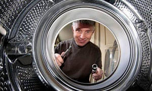 Man staring into a broken washing machine with spanners in hand