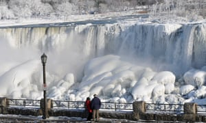 Visitors look at the frozen falls on the US side of Niagara falls.
