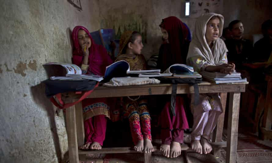 Afghan refugees and internally displaced Pakistani girls attend their classes at a makeshift school.