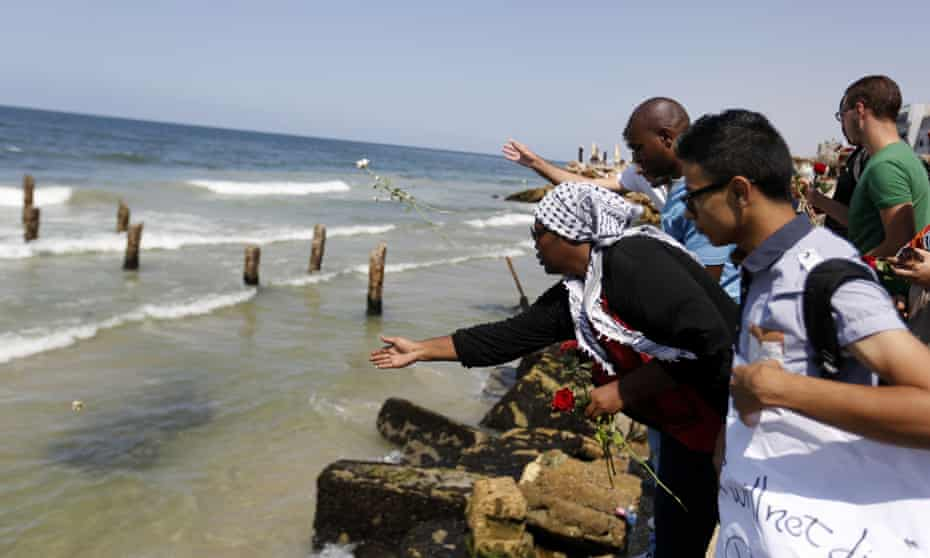 Palestinians throw roses in the Mediterranean sea off the coast of Gaza City