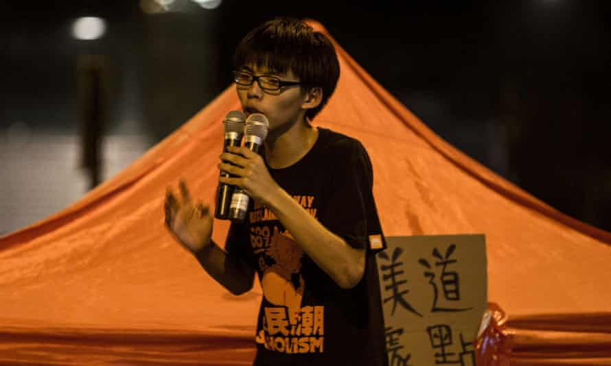 Joshua Wong speaks to fellow students on the street outside the Hong Kong Government Complex.
