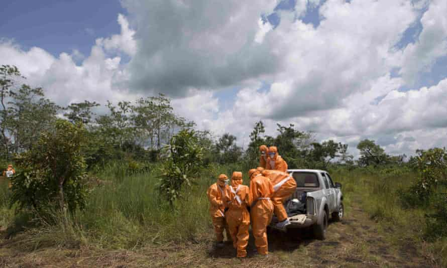 A burial team wearing protective clothes prepare an Ebola virus victim for interment, in Port Loko, Sierra Leone.