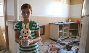 """Aleh: """"This is my second-favourite toy, Foo. She sleeps with me at night and I covet her like she is my own daughter:"""" Aleh's family now sleep in the bathroom, one of the only rooms left in their house.  Aleh's favourite toy, a bridesmaid doll, was lost in the wreckage."""
