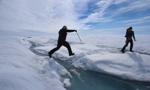 Scientist Ian Joughin of the University of Washington leaps over a small meltwater stream as he walks with Graduate Student, Laura Stevens, from the Massachusetts Institute of Technology and Woods Hole Oceanographic Institution as they conduct research on July 16, 2013 on the Glacial Ice Sheet, Greenland.