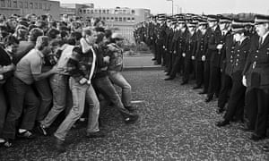 Striking miners facing line of police