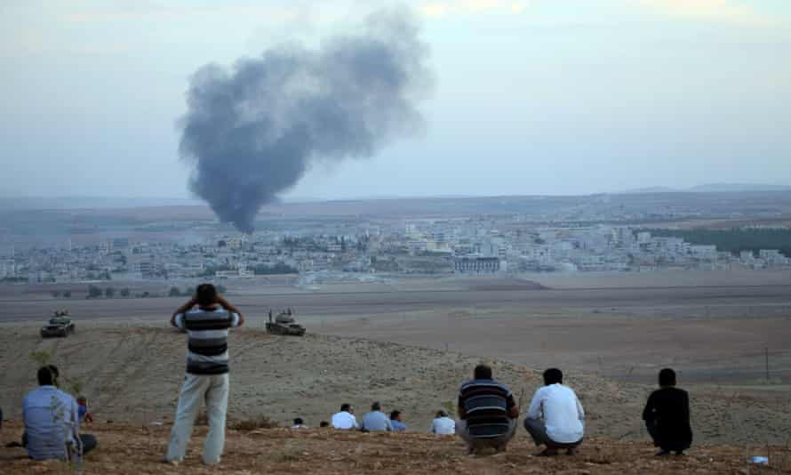 People watch the clashes between Isis and Kurdish armed groups in Kobani.