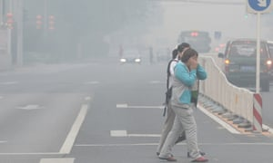 Pedestrians covering their faces as they cross a street in Beijing amid heavy smog.