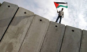 A man stands on the wall along the border with Israel and waves a Palestinian flag