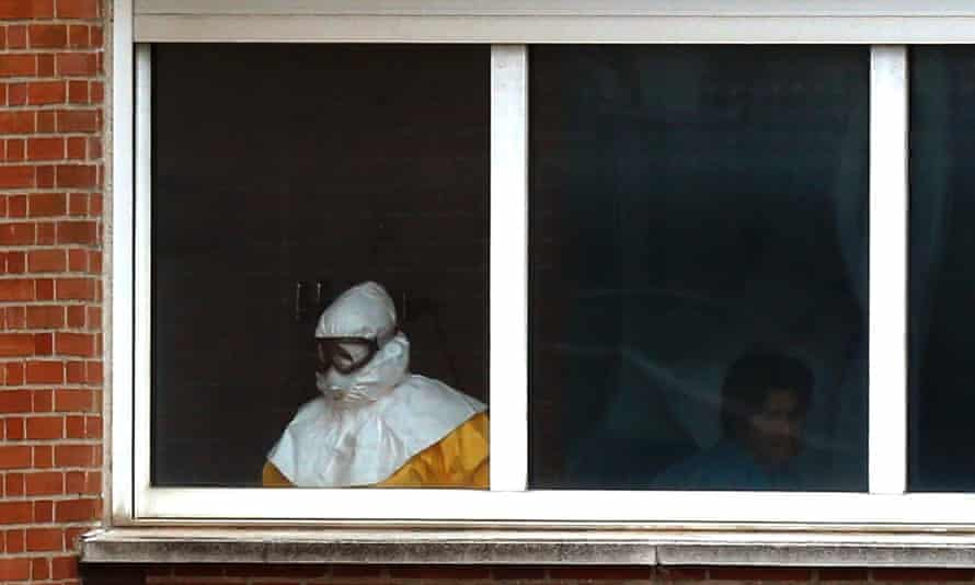 A medical practitioner wearing protective clothing treates an isolated patient on the sixth floor of the the Carlos III hospital in Madrid, Spain.