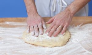 A man kneading bread dough