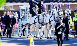 Family members of murder victim Hannah Witheridge walk behind a horse-drawn hearse carrying her coffin.