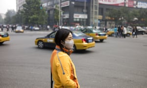 A woman wears a face mask on the street in Beijing amid heavy smog.