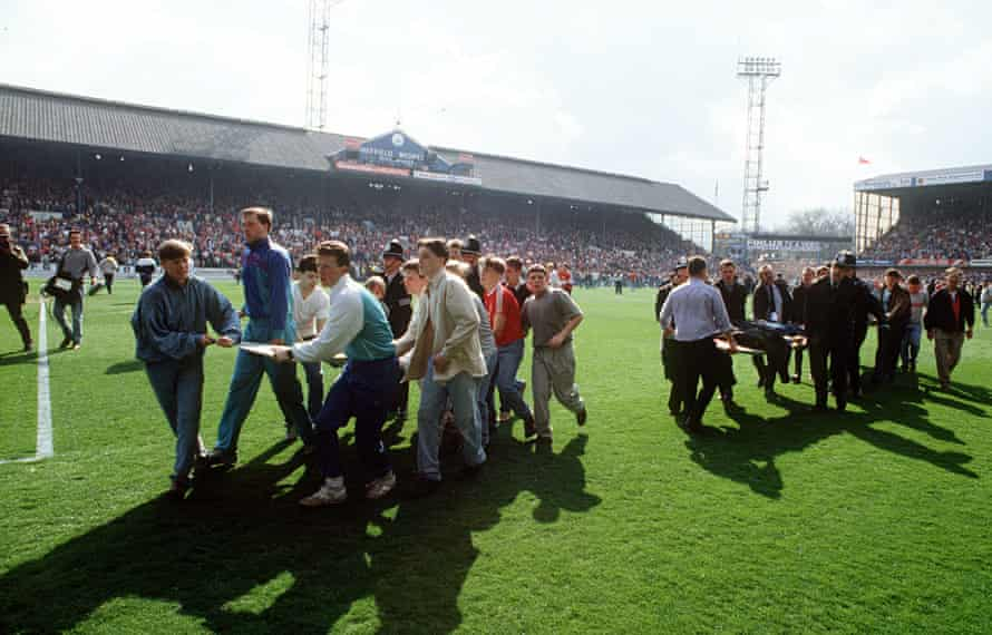 Supporters use advertising boards to carry injured fans out of Hillsborough stadium. The police clai