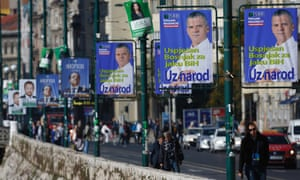 A Bosnian woman passes by election posters  in Sarajevo.