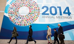 People walk past a sign for the World Bank/IMF annual meetings in Washington