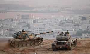 Turkish army tanks keep watch from their side of the border over the Isis-besieged Syrian town of Kobani.