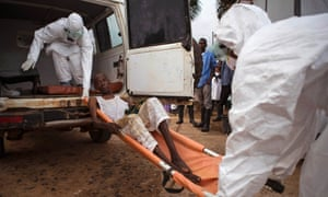 Healthcare workers load a man suspected of suffering from the Ebola virus onto an ambulance in Kenema, Sierra Leone.