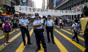 Police stand in front of a banner in Hong Kong
