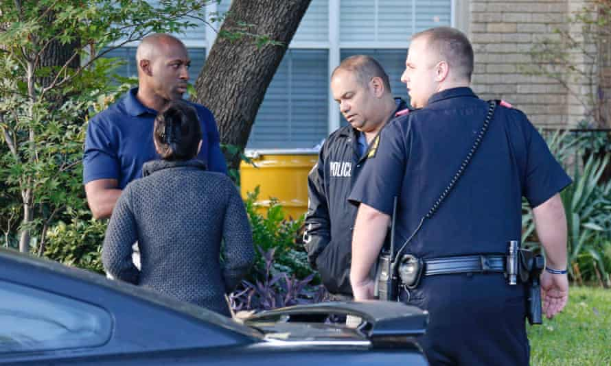 Police confer as a barrel for disposal of hazardous waste sits outside the apartment of the health worker.