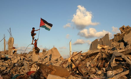 Palestinian children in Khan Yunis on the Gaza Strip place their national flag on the rubble of a bu