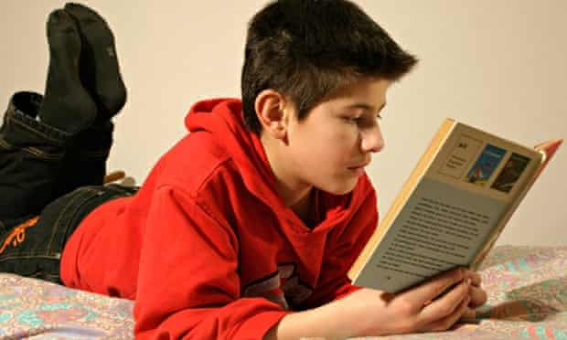 portrait of a young boy reading a book