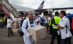 Cuban healthworkers unload medical supplies at Freetown's airport to fight Ebola in Sierra Leone