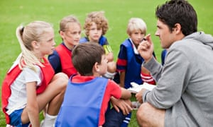 Football coach talking to his young team