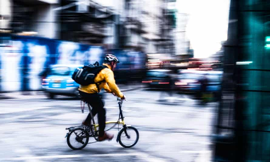 Cyclist wearing a bright Yellow jacket is taking a right turn into Tottenham Court Road, London