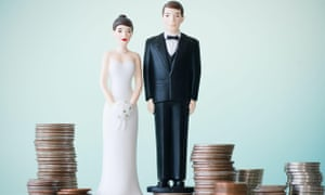 Wedding cake figurines on stacks of coins