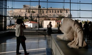 Visitors to Athens' Acropolis Museum look at the view to the ancient Temple of Parthenon.
