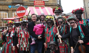 David Cameron poses with black-faced morris dancers