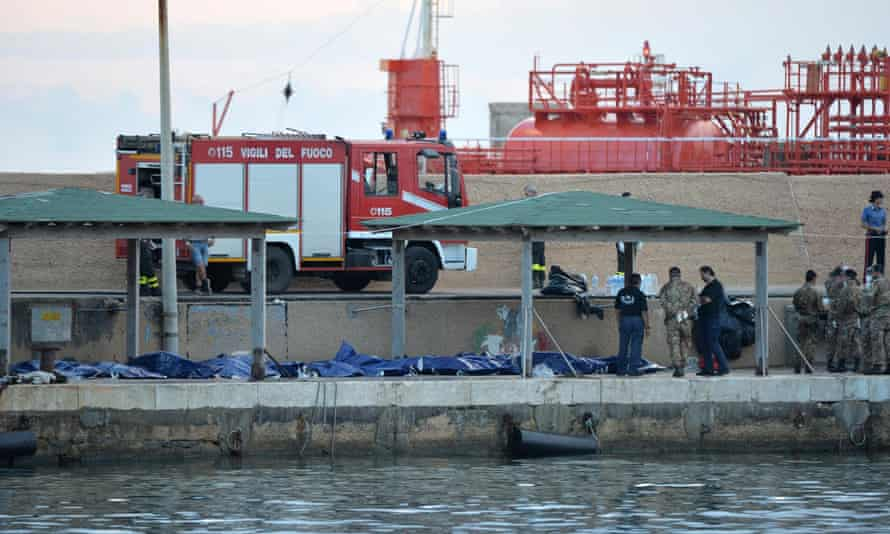 Officials stand over the bodies of some of the African migrants killed in a shipwreck off the Italian coast in Lampedusa.