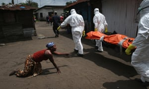 A woman crawls towards the body of her sister as Ebola burial team members take her sister Mekie Nagbe, for cremation in Monrovia, Liberia.
