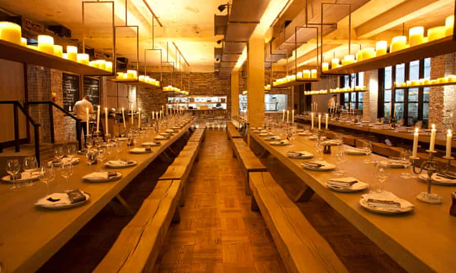 Long communal tables with benches and candles on a hanging shelf at Beast