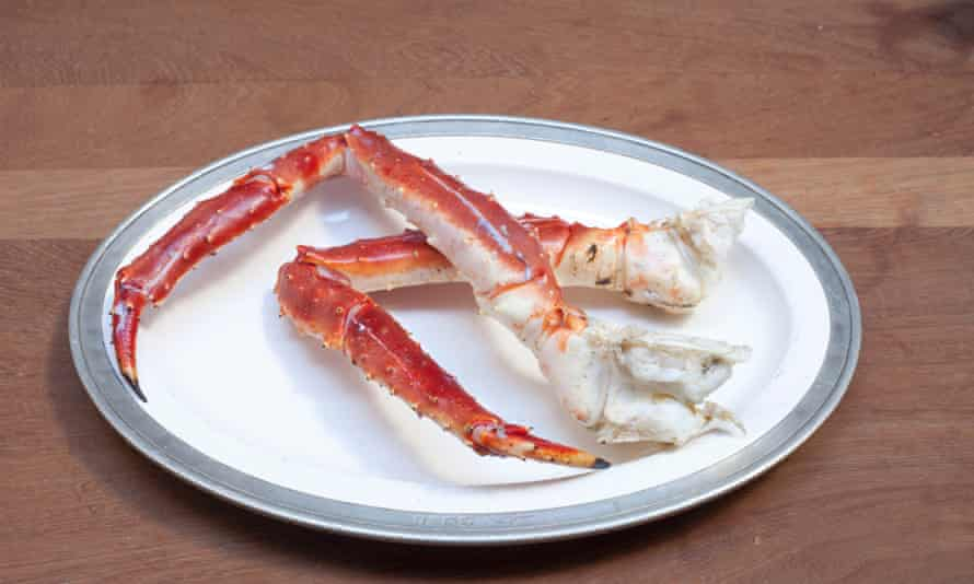 Two crab legs bent on a plate.