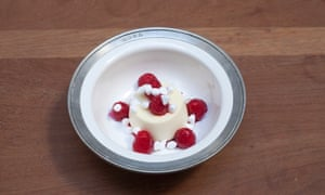 A round lemon mousse with five raspberries around it and one on top