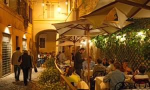 People sitting on a restaurant terrace in Trastevere, Rome.