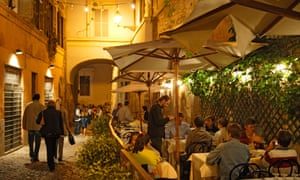 People sitting on a restaurant terrace in Trastevere, Rome.