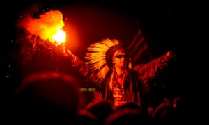 A man in the crowd wearing a Native American Headdress holding a lit flare as Jake Bug performs headlining The Other stage at Glastonbury
