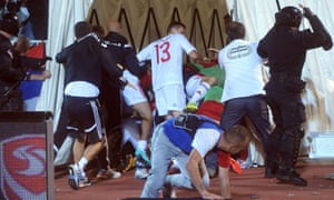 Players run for cover as the crowd throws objects towards the tunnel.