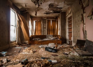 The Ashtabula County mansion's living room has paper peeling off the walls, holes in the ceiling and paint cans strewn across the floor